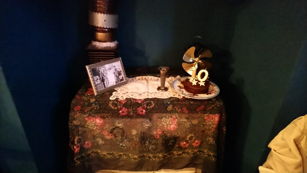 A dark floral table cloth with a vintage photoframe with an old photograph in.